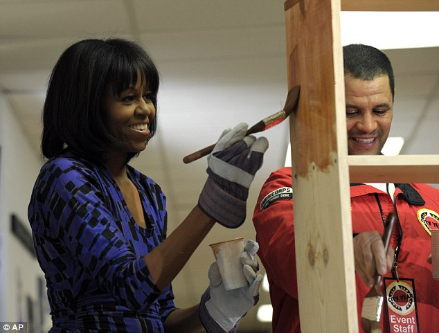 Joking: First lady Michelle Obama jokes with other volunteers as she paints a bookshelf