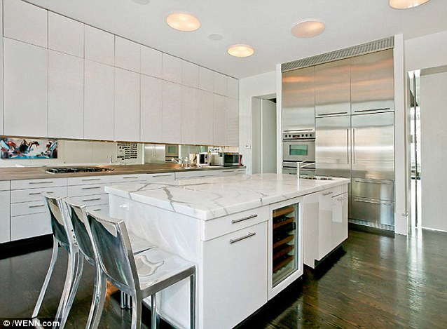 Extravagant: The white and chrome kitchen area has a marble counter top