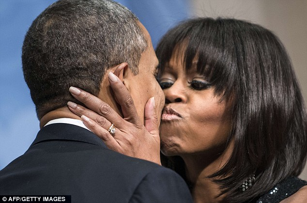 Four more years: Michelle Obama kisses Barack as the couple attend a celebration for their supporters in D.C. on Sunday night