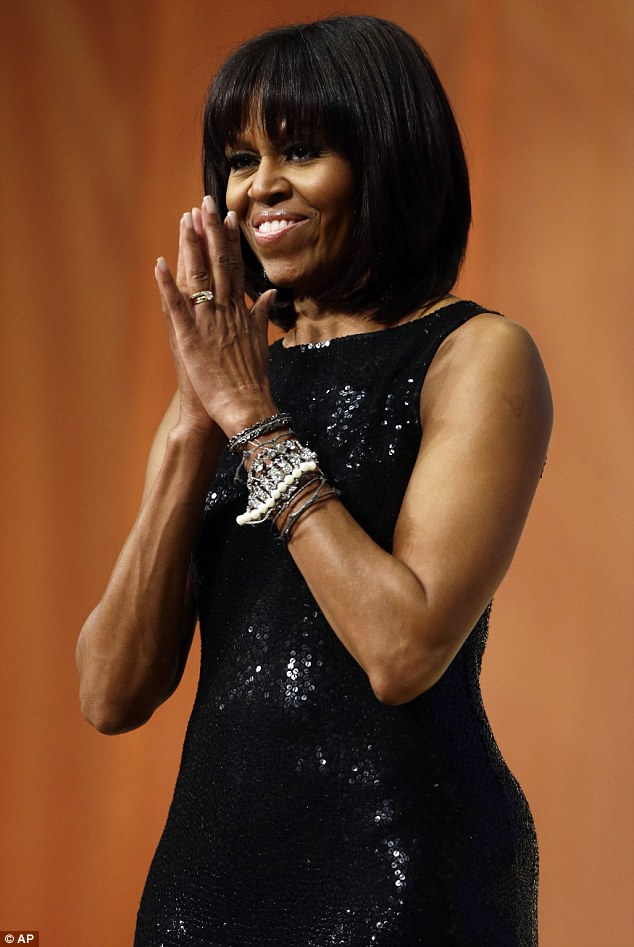 First lady of fashion: Michelle Obama wore a flattering and glamorous black sequined dress to the even with a collection of bracelets and statement earrings