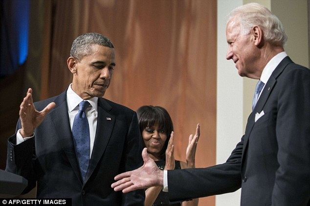 Shake on it: Obama and Biden on stage in front of hundreds of supporters on Sunday night as First Lady Michelle leads the applause