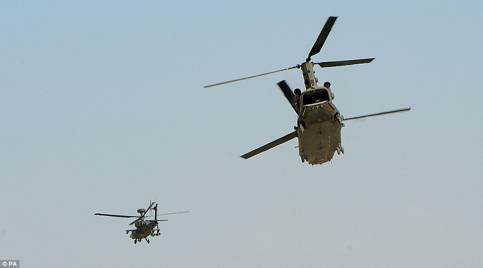 This previously unseen photograph shows Capt Wales flying off, left, as protection for a Chinook helicopter, right, above the British-controlled flight-line