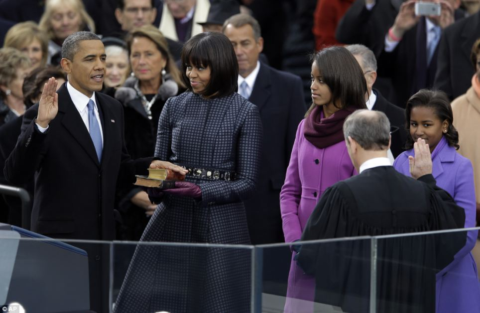 Swearing in: Obama's family and members of the Senate look on as he is sworn into office by Chief Justice John G. Roberts