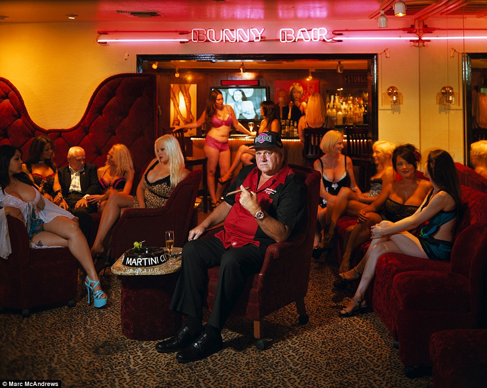 Showing off: Dennis Hof, the owner of the Bunny Ranch and and three other brothels, plays up the sex and glamor in his clubs. He is seen here surrounded by a few of his 'working girls' at the Bunny Ranch