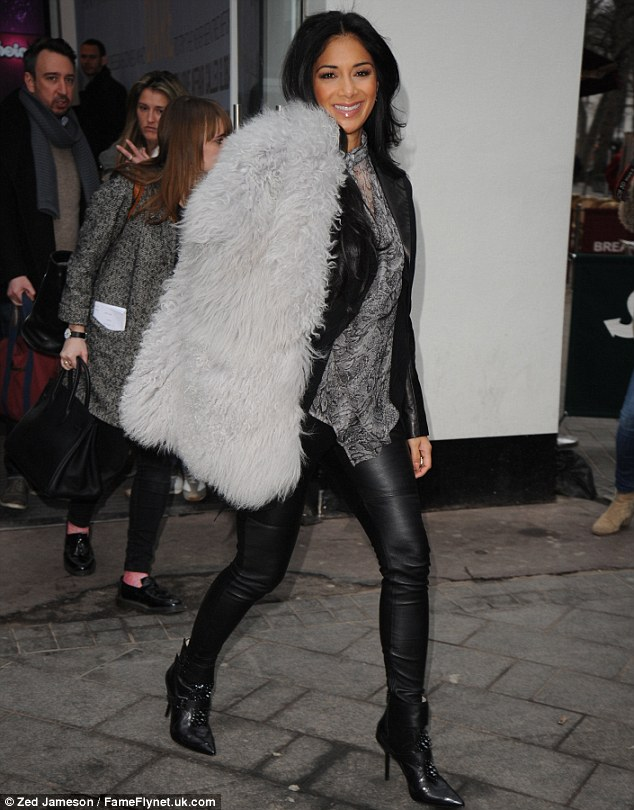 Feisty: The 34-year-old singer made sure to show she certainly meant business in a fierce ensemble of form-fitting leather trousers, a vampy black satin jacket and a sexy sheer snakeskin-print blouse