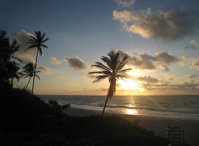 The sun sets on a Barbados' palm tree-fringed coastline