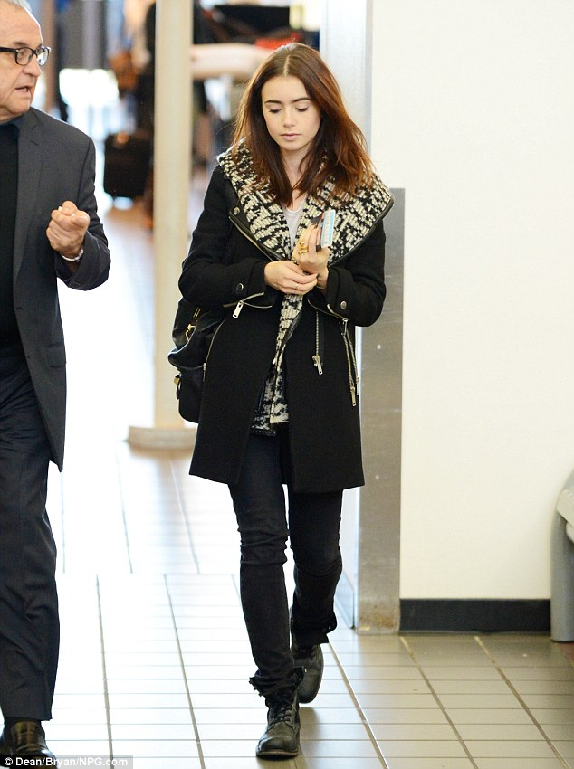 Lily Collins Makes An Unsmiling Departure Clutching Her