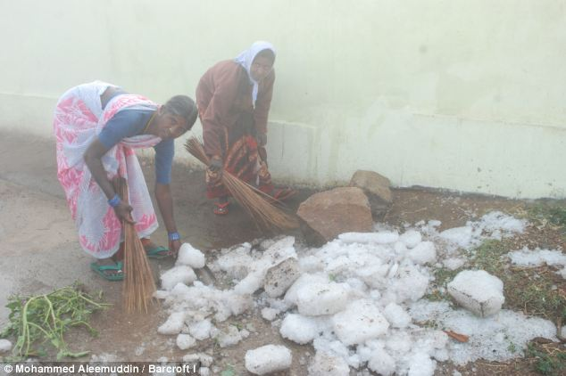 Raining down: People cleaning the streets covered with large boulders of hailstorm Andhra Pradesh, India