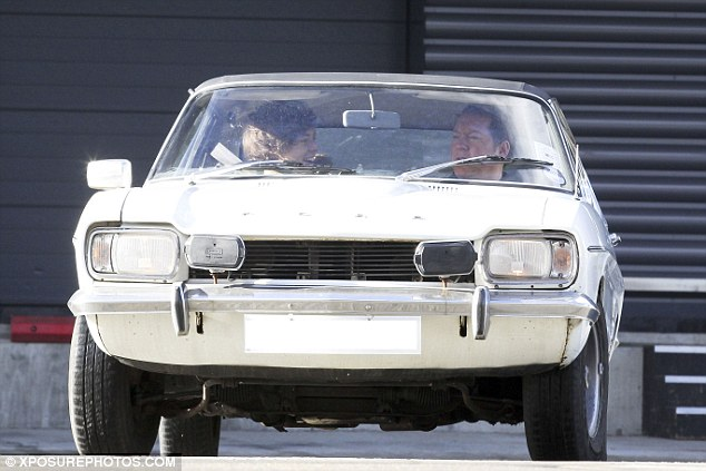 The smile says it all: The pop star was seen laughing and smiling in the car as he drove off once more