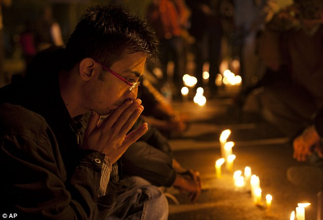 A dream destroyed: A man bows his head at a candlelit vigil for the 23-year-old student - affectionately called 'Bitiya', or 'little daughter' by her parents - who died after being gang-raped on a moving bus in New Delhi