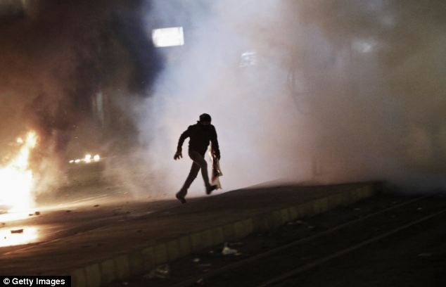 Demonstrate: A Egyptian protester runs through clouds of smoke and tear gas during clashes with riot police