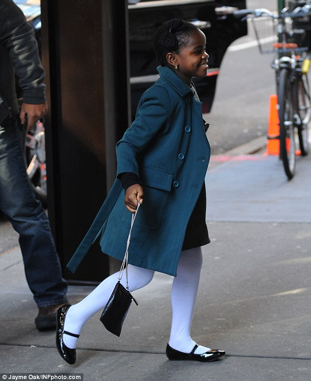 Looking smart: Unlike her mum, Mercy looks smart in a green coat and white tights as she heads into the centre