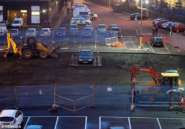 Marooned: Work continues around a luxury Mercedes that was parked on a building site