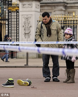 Tourists view the personal effects of a suspect at the scene between the Queen Victoria Memorial and Buckingham Palace