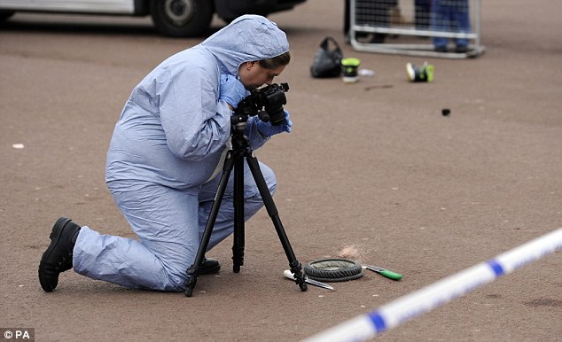Up close: A scenes of crime officer photographs a hat and two knives from the scene in central London