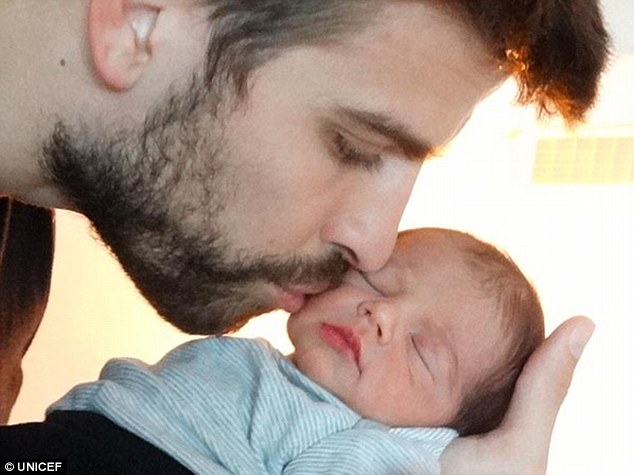 Welcome to the world! The very first picture of Shakira's newborn Milan shows him cradled by his father Gerard Pique; the couple have asked for donations to Unicef in his name