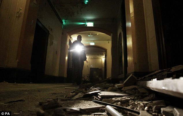 A Council worker shines a torch over debris on the floor of the corridor in the now derelict Sisters of Our Lady of Charity Magdalene Laundry in Dublin