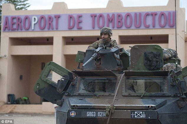 Liberator: A French soldier mans the gun of an armoured vehicle as he stands guard in front of the airport in Timbuktu