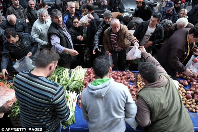 Taking action: Greek farmers give away fruit and vegetables as part of their protest against high production costs, earlier today