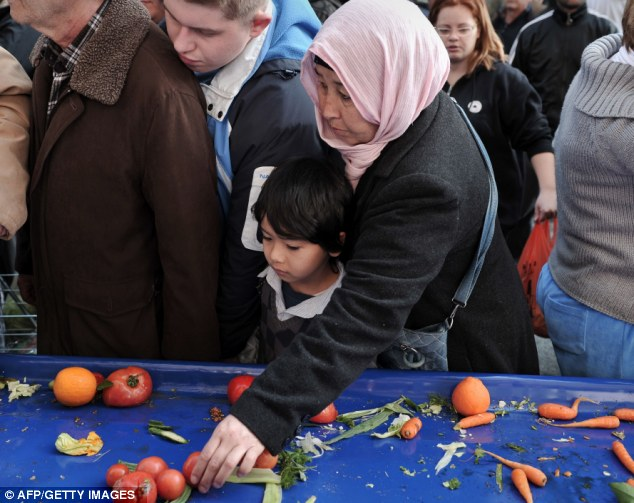 Scraps: A woman and a young child reach for the last broken tomatoes on a table
