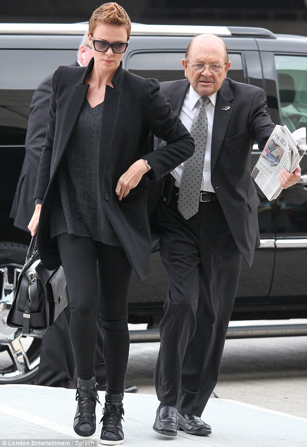 Mystery man: Charlize was joined by an older gentleman as she made her way into the LAX airport