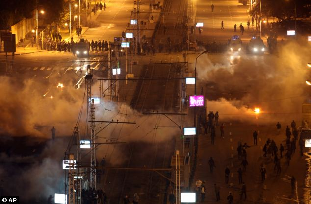 WINTER OF DISCONTENT As they gather: Police fired into the air, shot teargas and drove cars toward the crowd to scatter protesters as they gathered outside the presidential palace