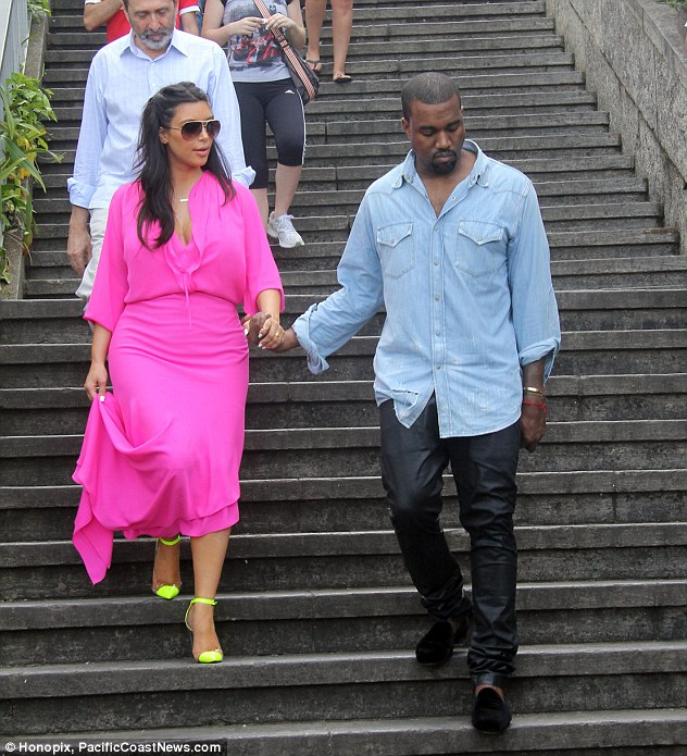 Not made for walking: Kim held on to Kanye's hand as she descended the stairs in her high heels