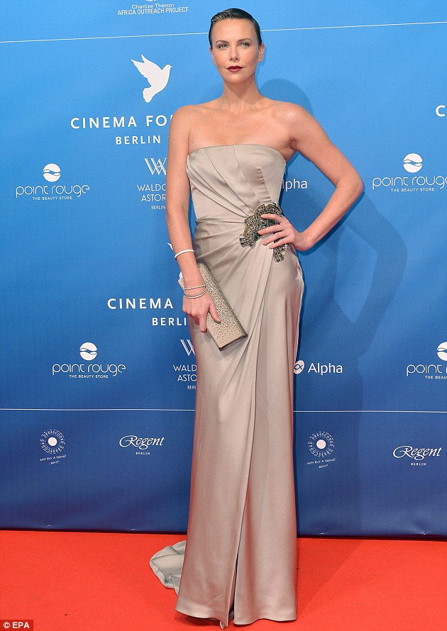 Elegantly hairless: Charlize Theron shines despite her buzz cut on the red carpet for the charity event Cinema For Peace in Berlin, Germany
