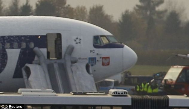 Miraculous: Passengers escaped down the plane's emergency chutes after the landing at Warsaw. No one was injured