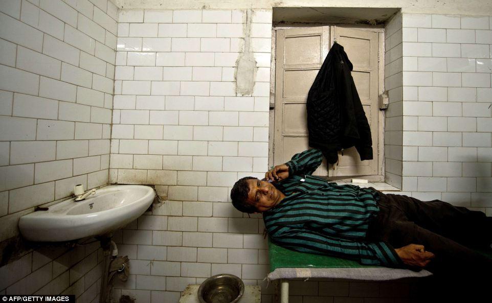Вред: Раджеш, 45, переговоры по мобильному телефону, как он лежит на кровати в больнице РЖД в Аллахабаде на после ранения в давке