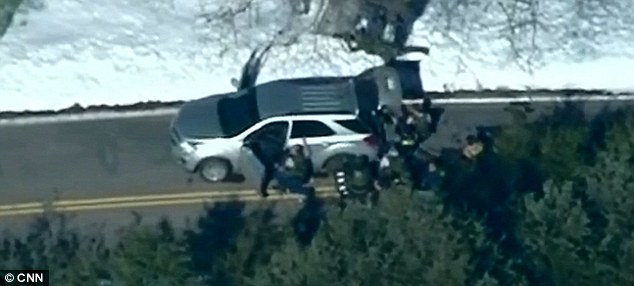 Holding out: Officers used their SUV as cover as they took up positions around the cabin