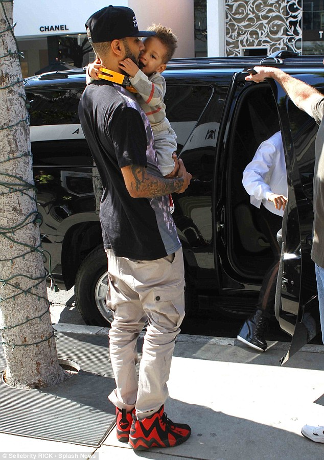 Daddy's boy: Little Egypt nuzzled into his father after the clan left the Newsroom cafe in West Hollywood