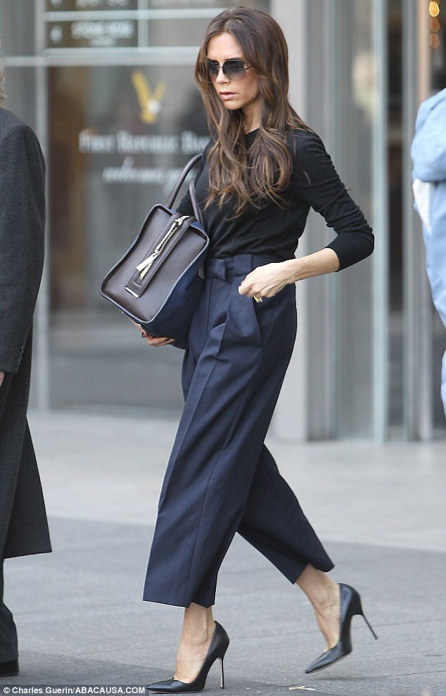 Chic: Victoria was wearing navy trousers, a long-sleeved black T-shirt and high heels