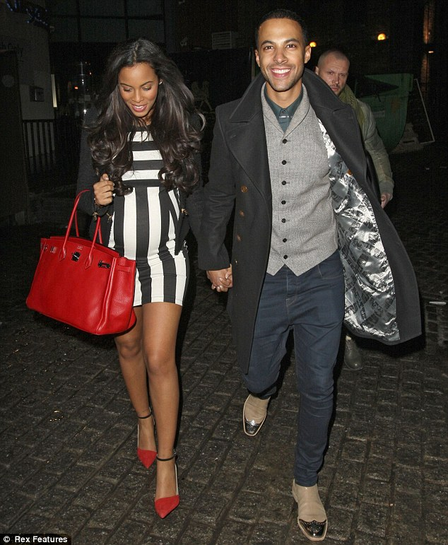 All lined up: Rochelle teamed her black and white dress with a red handbag and a pair of high heels