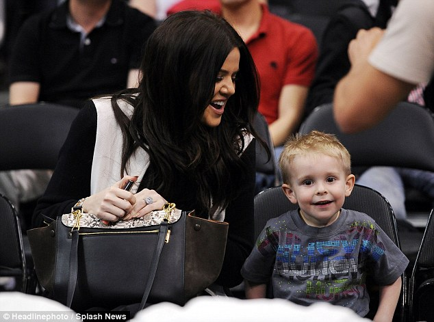 A little support: Khloe was entertained by one small fan who was enjoying the big game
