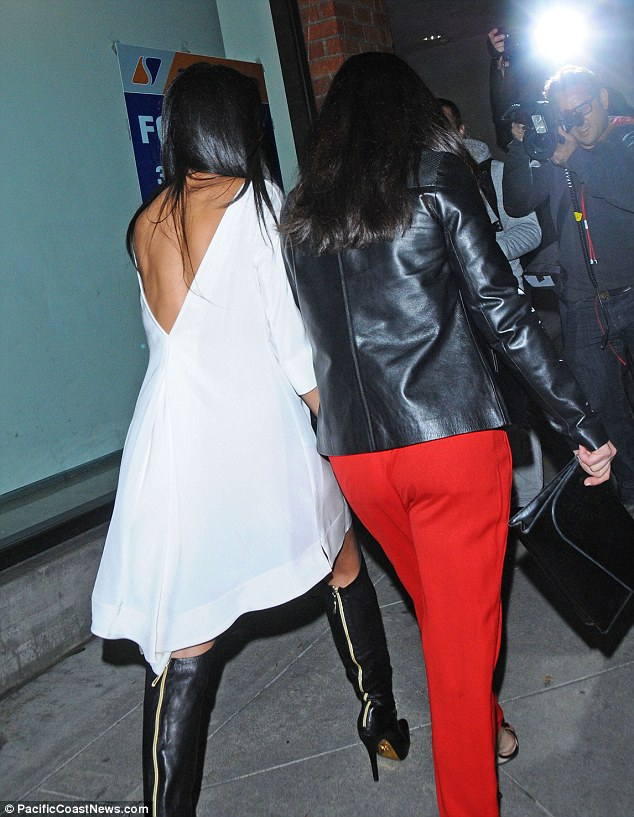 Sexy back: Nicole showed off the cut of her frock and the zip detailing of her heeled boots as she headed inside with a girl pal