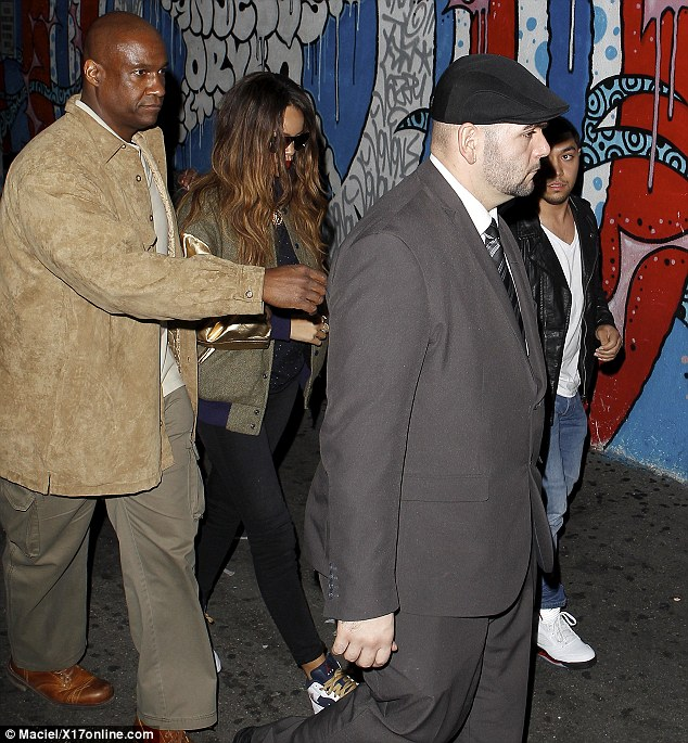 Hide me: Rihanna was surrounded by bodyguards as she entered the club without her on-again off-again paramour Chris