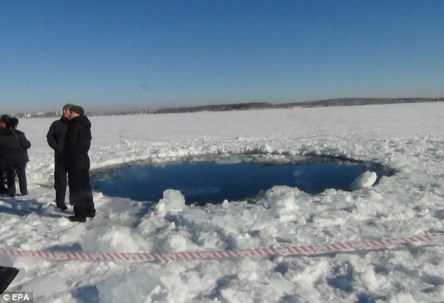 Investigation: Officials stand around the hole caused by the meteorite strike, which also set off a dangerous sonic boom
