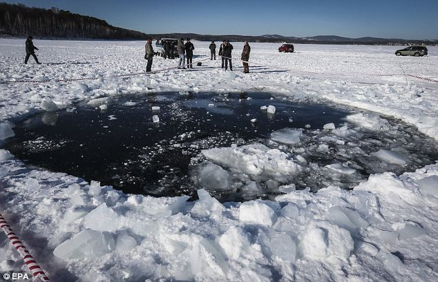 Ice hole: Experts said the meteor that left a 50-foot hole in a frozen lake on the outskirts of Chelyabinsk, in the Urals, weighed around 100,000 tonnes and measured 55 feet in diameter