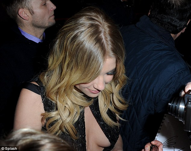 Be careful! Ashley came in danger of falling out of her dress as she was surrounded by fans