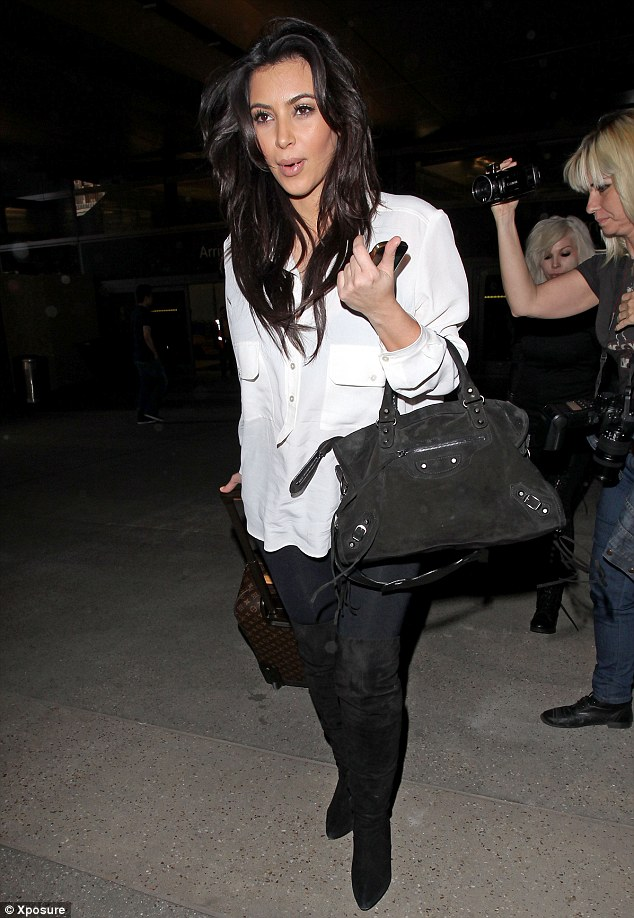 Ready for bed: Kim Kardashian arrives home from Nigeria looking tired after her brief stay in the African country