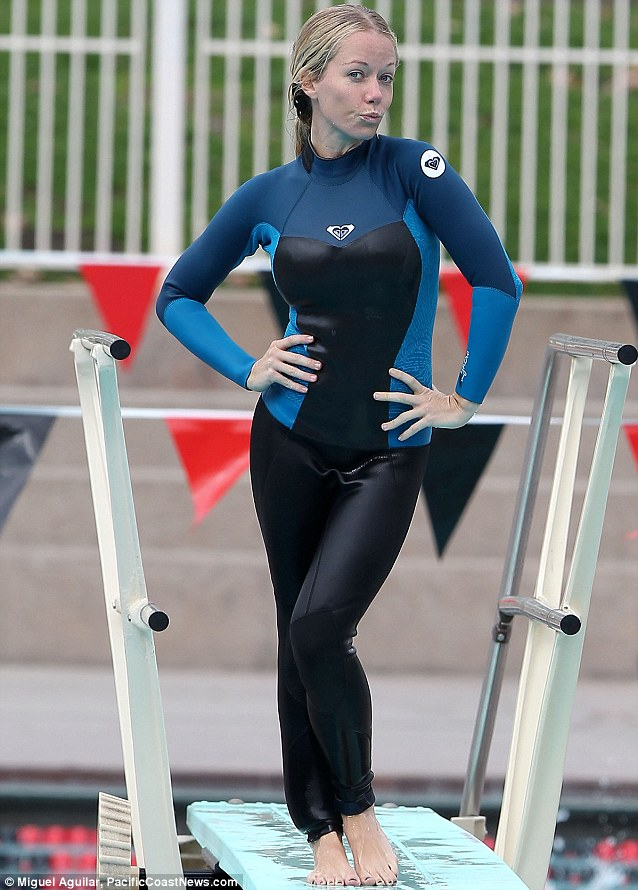 Much more demure: Pouting Kendra later practised her dives wearing a blue and black wetsuit