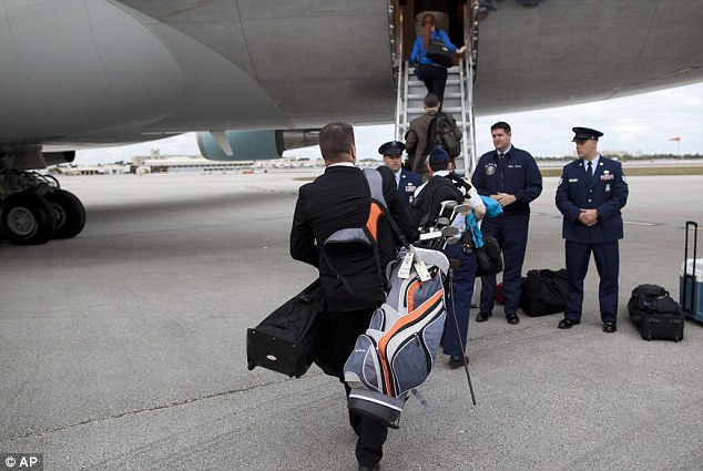 Extra baggage: A White House aide carries the golf bag of Eric Whitaker, Obama's long-time friend, aboard the plane after their boys' weekend at a luxury golf resort