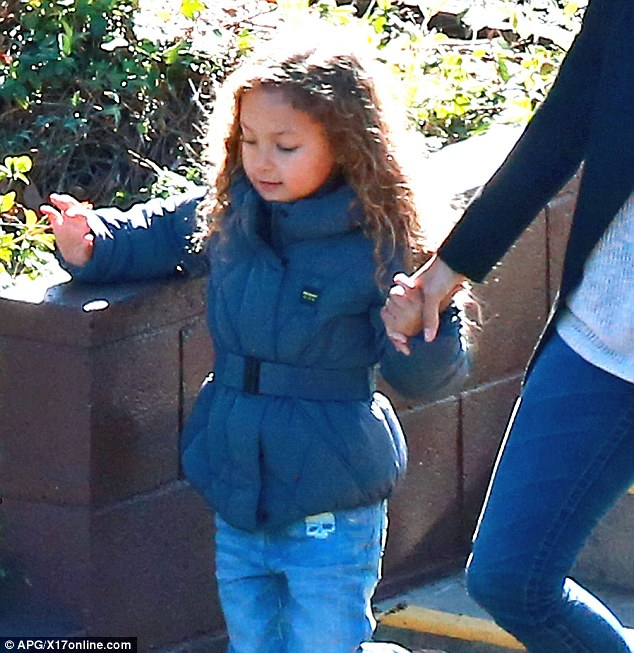 Happy in the sun: Nahla looked playful as Halle led her by the hand to school