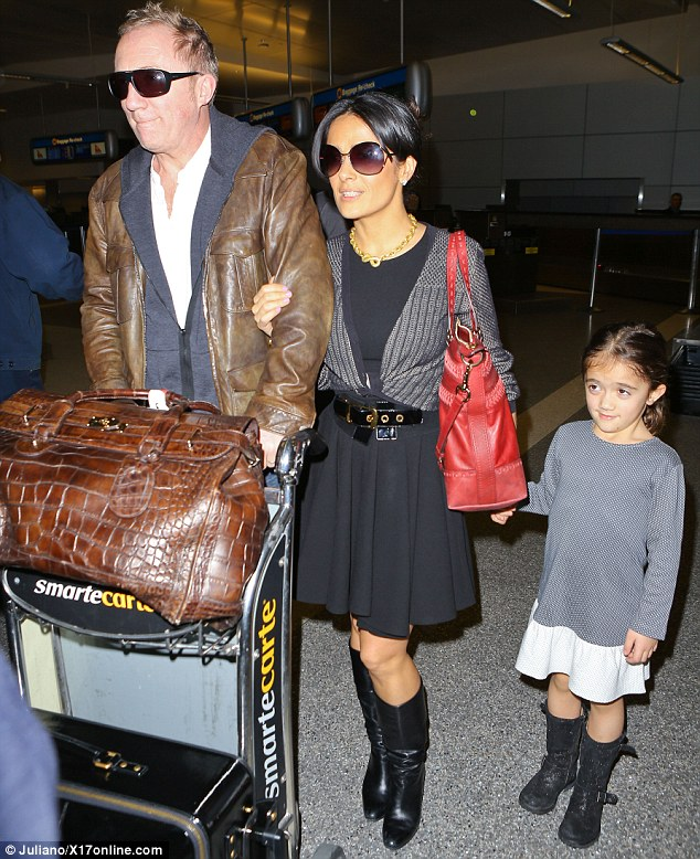 Travelling in style: Salma looks chic as she arrives with her family from Milan