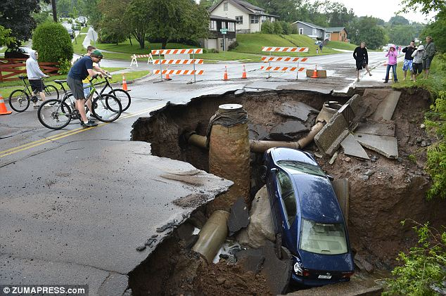 Fearless: These intrepid teenagers and neighbors were unafraid of the edge of the sinkhole in Duluth, Minnesota that came after a flash flood of 9-inches of rain the night before