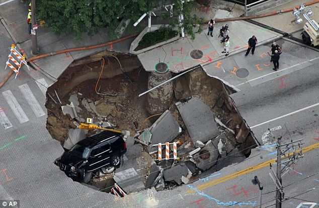 Sudden impact: A Cadillac Escalade fell into a Milwaukee sinkhole in 2010 and though the driver was able to escape, the car was still running 20 hours after it first fell