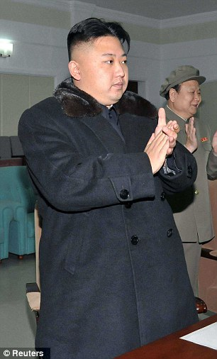 North Korean leader Kim Jong-Un claps at the General Satellite Control and Command Center after the launch of the Unha-3 rocket