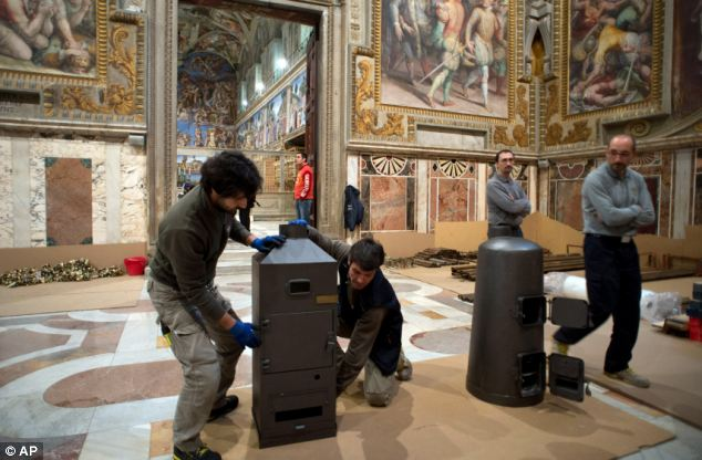 Preparations: Workers are pictured installing the stoves where ballots are burned during Conclave