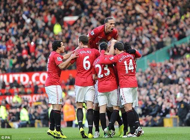 High life: Rooney is mobbed after scoring United's second goal (above, as United striker Robin van Persie (below) watches from the bench